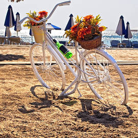 Bicycle Parked On A Beach Next To The Umbrellas by Flavio Vieri
