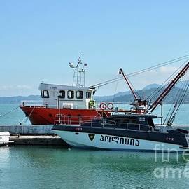 Boats and tugboats at marina with Georgian flag Batumi harbor Georgia by Imran Ahmed