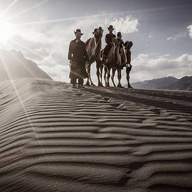 Camel riders on the crest of a sand dune in the Nubra Valley by Murray Rudd