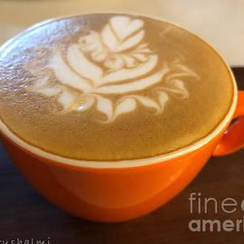 Cappuccino Art in orange cup by Noa Yerushalmi
