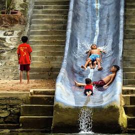 Children having fun on a water slide by Anita Gendt van