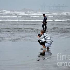 Chinese man squats with camera taking photo at Sea View beach water Karachi Pakistan by Imran Ahmed