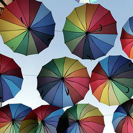 Colorful rainbow umbrellas summer decoration, hung over the street, photo series 3. by Akos Horvath