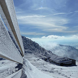 Fairy-tale view on old snowy cottage on the top of Chopok mountain in national park Low Tatras in Slovakia. Paradise same as in Alps. Snowy and frost wooden wall and pieces of top of mountain by Vaclav Sonnek