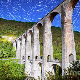 French old stone viaduct arch bridge architecture under moonlight with star trail in summer sky nigh by Gregory DUBUS