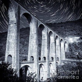 French old stone viaduct architecture under moonlight with star trails monochrome by Gregory DUBUS