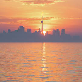 From Purple to Orange - Silhouetted Toronto Skyline Dividing the Rising Sun Disk by Georgia Mizuleva