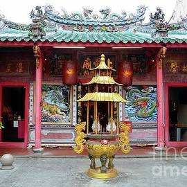 Golden urn and guard lions at entrance to Chinese temple Kuching Sarawak Malaysia by Imran Ahmed