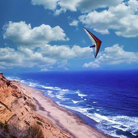 A Hangglider Soars Over The California Beach
