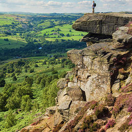 Hiker standing alone on Froggatt Edge, Derbyshire Peak District National Park, England by Neale And Judith Clark