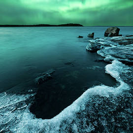 Ice on the lake shore and northern lights landscape by Juhani Viitanen