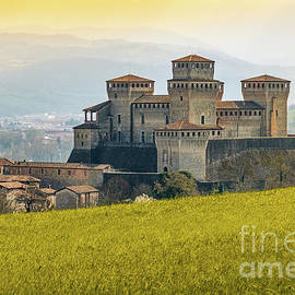 landmarks of italy, the Torrechiara fantasy castle near Parma - Italy with yellow warm toned grass a by Luca Lorenzelli
