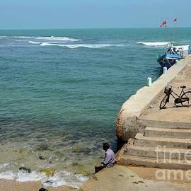 Man dips feet in water at beach pier with fishing vessel  near steps in Jaffna Sri Lanka by Imran Ahmed