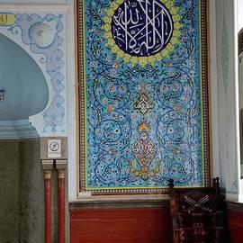 Man sits by Islamic wall mural mosaic art interior of central Muslim mosque Tbilisi Georgia by Imran Ahmed