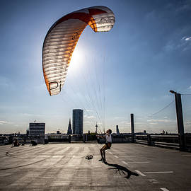 Man with paraglider in top of building by Rick Neves
