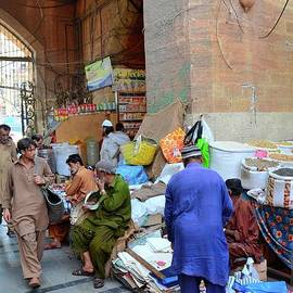 Men and coolies mill around arched entrance to Empress Market shops Saddar Karachi Pakistan by Imran Ahmed