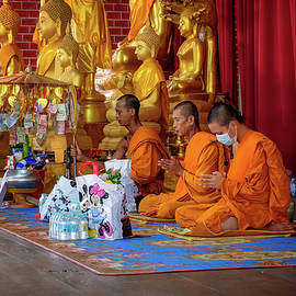 Monks pray after receiving donations at the local temple. by Lee Craker