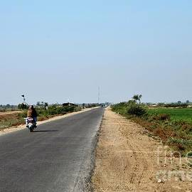 Motorcyclist on rural road surrounded by green farm fields near Mirpurkhas Sindh Pakistan by Imran Ahmed