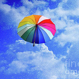 Multicolored umbrella flying suspended over bright blue sky back by Joaquin Corbalan
