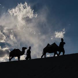 Nomads traversing sand dunes by Murray Rudd