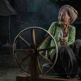 Old Balinese lady with her spinning wheel by Anges van der Logt