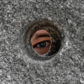 Open Eye Looking Through Round Hole In Stone Wall by Andreas Berthold
