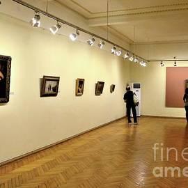 Painting artworks hang on wall while visitors view Adjara  Art Museum Batumi Georgia by Imran Ahmed