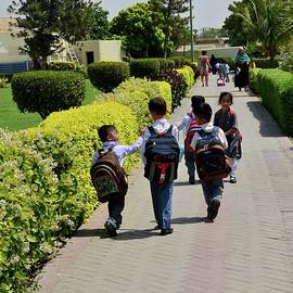 Pakistani schoolchildren with backpacks and uniforms walk towards classes Karachi Pakistan by Imran Ahmed