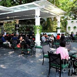 Patrons at outdoor street side upscale cafe in Old Quarter Hanoi Vietnam by Imran Ahmed