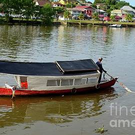 River ferry with boatman steers boat to landing jetty pier across Sarawak River Kuching Malaysia by Imran Ahmed