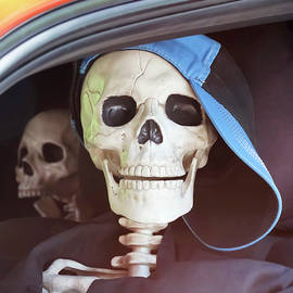 Seatbelts Uncool? A Pair of Teen Skeletons Sitting in Traffic by Derrick Neill