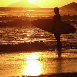 Surfer woman with surfboard in Brazilian beach at sunset by Rick Neves
