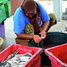 Thai Muslim woman in sarong and headscarf guts and cleans fish Pattani Thailand by Imran Ahmed