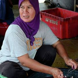 Thai Muslim woman in sweat pants and hijab headscarf guts and cleans fish Pattani Thailand by Imran Ahmed