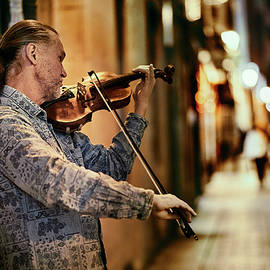 Violinist playing in the street at night by Sergio Florez Alonso