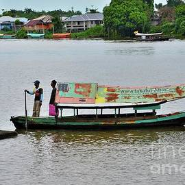 Weathered boat with sailor passenger and solar panel crosses Sarawak River Kuching Malaysia by Imran Ahmed