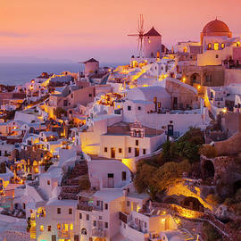Windmill and white houses at sunset, Oia, Santorini, Greece by Neale And Judith Clark