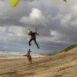 woman flying the paraglider and playing with the dog in Netherlands by Rick Neves