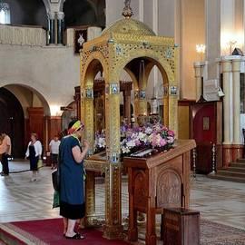 Woman prays at altar inside Holy Trinity Cathedral Sameba orthodox church Tbilisi Georgia by Imran Ahmed