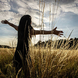 Woman with open arms in field by Rick Neves