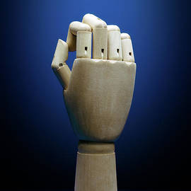 Wooden hand on classic blue background by Etienne Outram