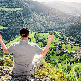 Young men meditating after hiking in front of French small village by Gregory DUBUS