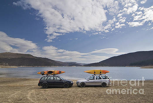 Cars and kayaks at a lake by Peter Til