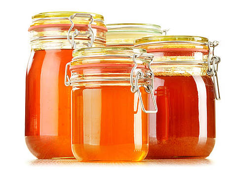 Composition with jars of honey isolated on white by T Monticello