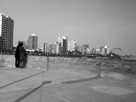 Couple looking at the horizon a parachute drop by Luis Fernando Del Aguila Mejia