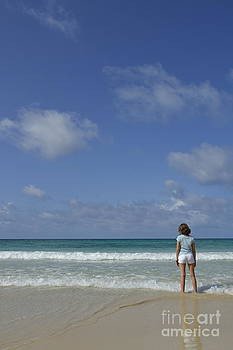 Girl contemplating ocean from beach by Sami Sarkis