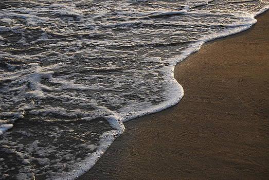 Sea foam on beach sand by Jocelyn Friis