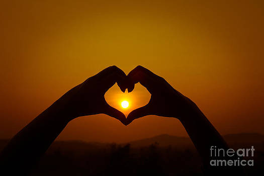 Silhouettes hand heart shaped by Tosporn Preede
