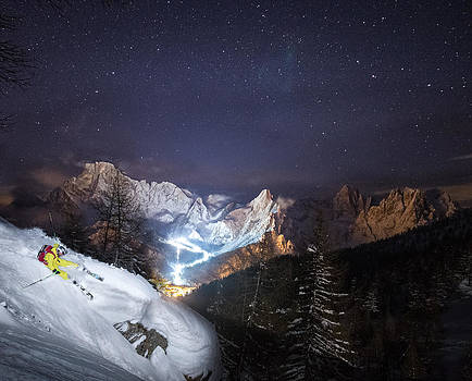 Skier riding down a powder slope at night by Leander Nardin