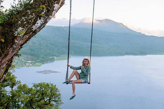 Woman Sitting On Swing Against Lake by Konstantin Trubavin